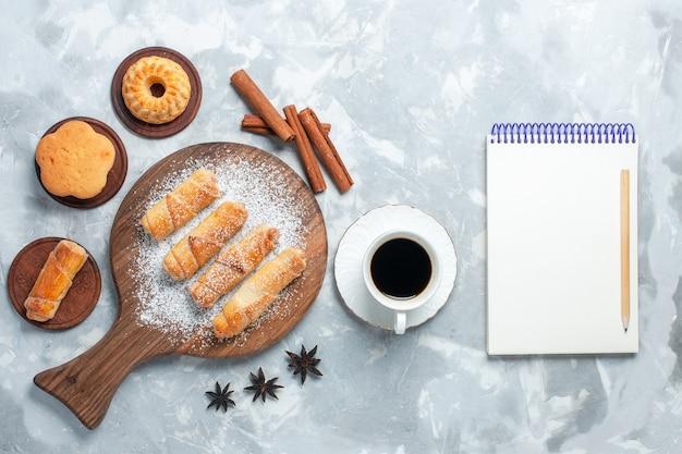 明るい白の背景にお茶とシナモンのカップとおいしいベーグルの上面図。