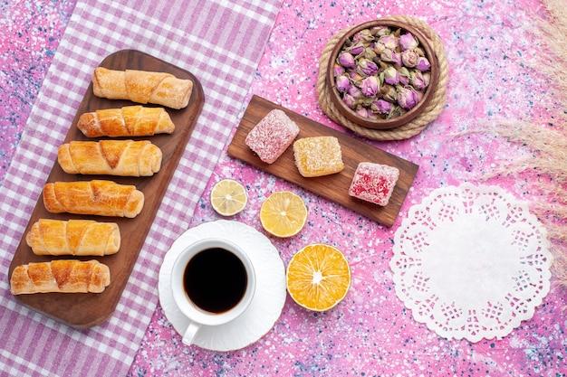 ライトピンクの背景にお茶とマーマレードのトップビューおいしいベーグル。