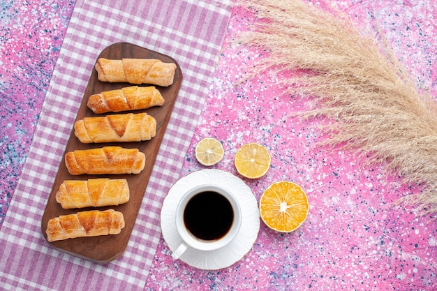 ピンクの背景にお茶を入れたトップビューのおいしいベーグル。