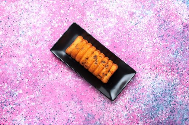 Вид сверху вкусный испеченный торт внутри черной формы для торта на розовом фоне.