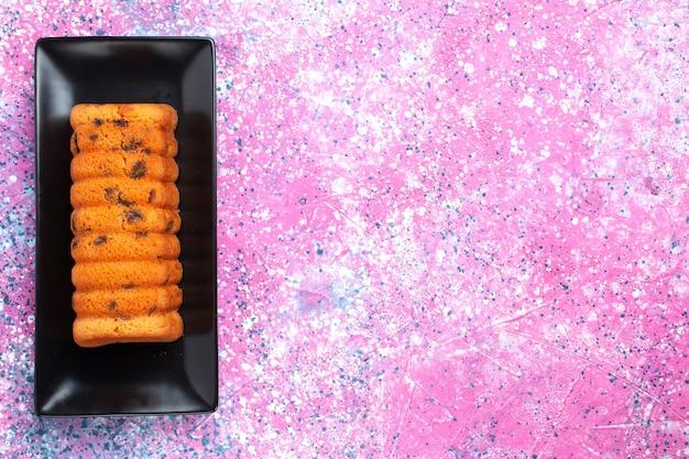 Вид сверху вкусный испеченный торт внутри черной формы для торта на розовом столе.