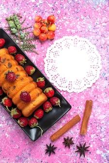 Вид сверху вкусный испеченный торт внутри черной формы для торта со свежей красной клубникой и корицей на розовом столе.