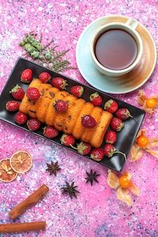 Вид сверху вкусный испеченный торт внутри черной формы для торта со свежей красной клубникой и чашкой чая на розовом полу.