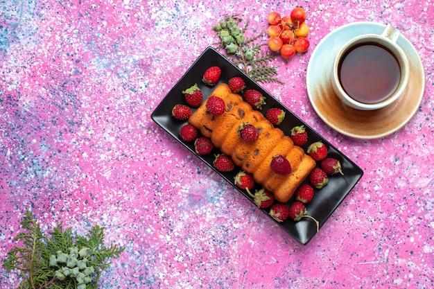 Вид сверху вкусный испеченный торт внутри черной формы для торта со свежей красной клубникой на розовом столе.