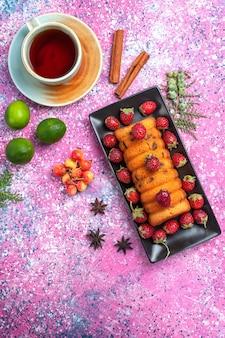 Вид сверху вкусный испеченный торт внутри черной формы для торта со свежим красным чаем клубники и лимоном на розовом столе.