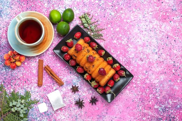 Вид сверху вкусный испеченный торт внутри черной формы для торта со свежим красным чаем клубники и лимонами на розовом столе.