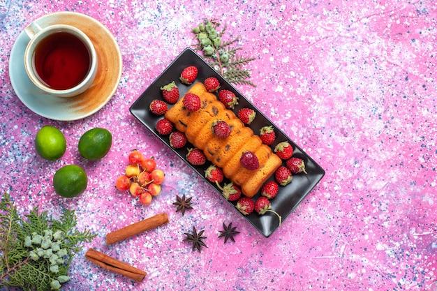 Вид сверху вкусный испеченный торт внутри черной формы для торта со свежей красной клубникой, чаем, корицей и лимонами на розовом столе.