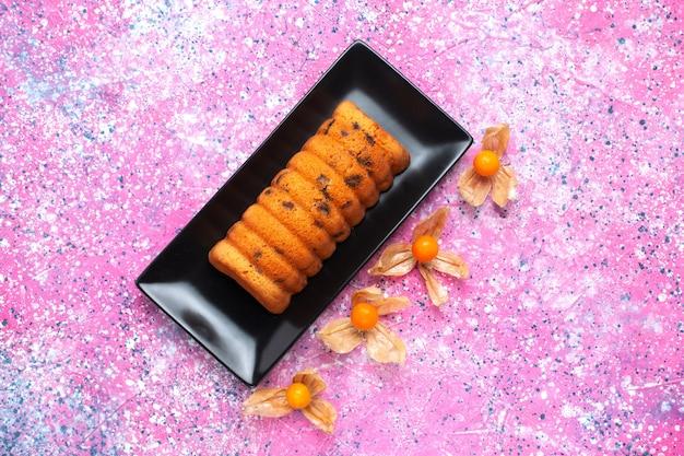 Вид сверху вкусный испеченный торт внутри черной формы для торта с физалисами на розовом столе.