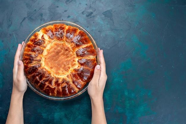 Vista dall'alto una deliziosa torta al forno tonda formata dolce all'interno della teglia di vetro sullo sfondo azzurro.