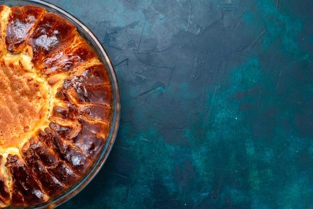 上面図水色の机の上のガラス鍋の中に甘い焼き菓子の丸い形ができました。