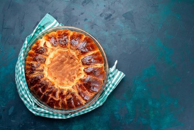 Вид сверху вкусный запеченный торт круглой формы сладкий внутри стеклянной сковороды на голубом полу.
