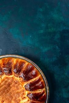 Вид сверху вкусный запеченный торт круглый сформированный сладкий внутри стеклянной сковороды на светло-синем фоне.