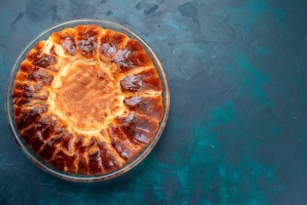 Вид сверху вкусный выпеченный торт круглой формы сладкий внутри стеклянной сковороды на голубом столе.