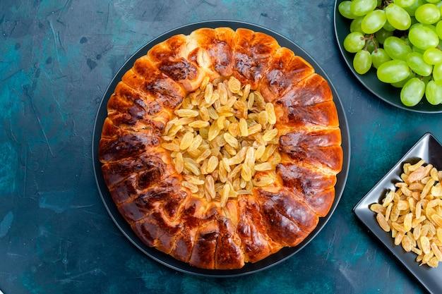 Вид сверху вкусный запеченный торт с изюмом и свежим зеленым виноградом на темно-синем фоне торт пирог сахарное сладкое бисквитное тесто