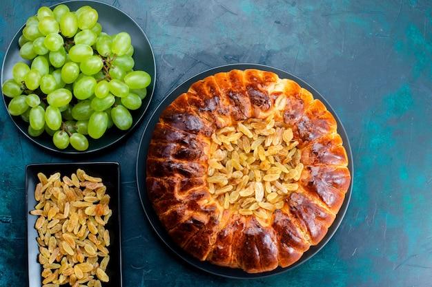 Vista dall'alto una deliziosa torta al forno con uvetta e uva verde fresca sullo sfondo blu scuro torta di zucchero torta dolce pasta biscotto