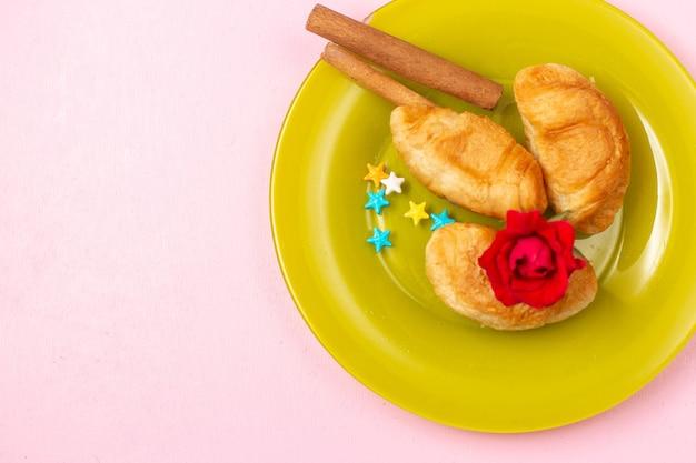 トップビューピンクの机の上の緑のプレートの内側にシナモンが入ったフルーツが入ったおいしい焼きたてのクロワッサン