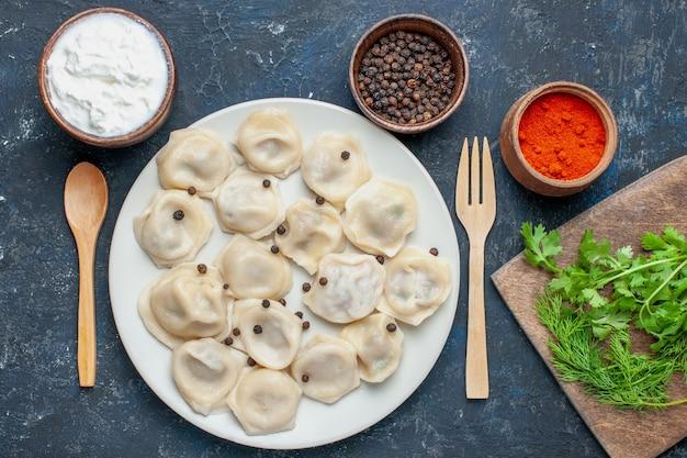 Vista dall'alto di deliziosi gnocchi al forno all'interno del piatto insieme a pepe e verdure su calorie scure, pasta pasto cena cibo carne