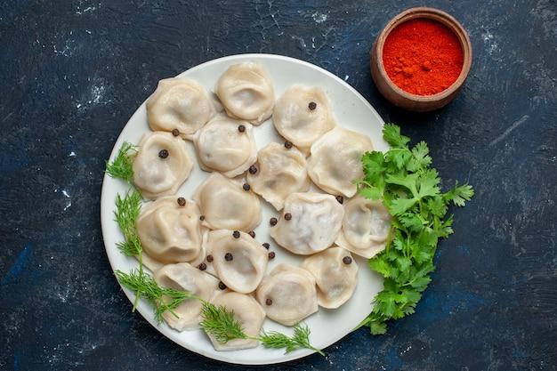 Vista dall'alto di deliziosi gnocchi al forno all'interno del piatto insieme a pepe e verdure sulla scrivania grigia, caloria di carne cena pasto pasta