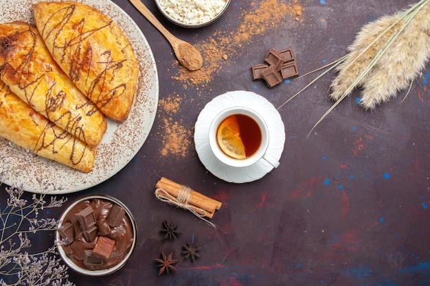 Вид сверху вкусной выпечки с творогом и чаем на темном пространстве