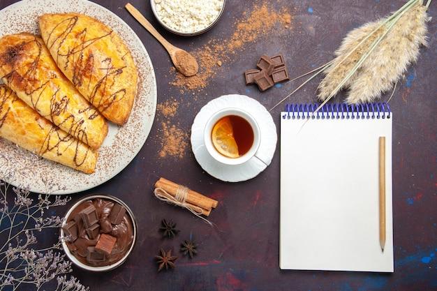 Вид сверху вкусной выпечки с творогом и чаем на темном столе