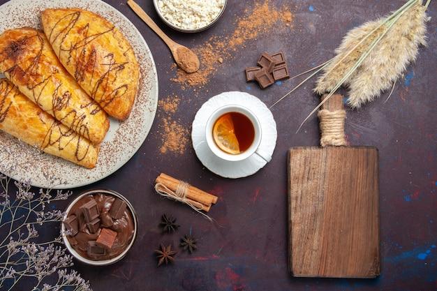 暗い空間でカッテージチーズとお茶とおいしい焼き菓子の上面図