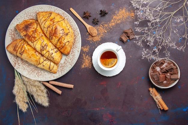 Вид сверху вкусной выпечки с чашкой чая на темном пространстве