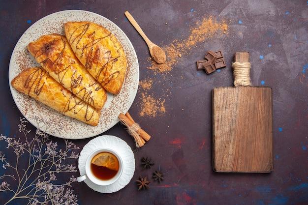 Vista dall'alto deliziosi pasticcini al forno con una tazza di tè nello spazio buio