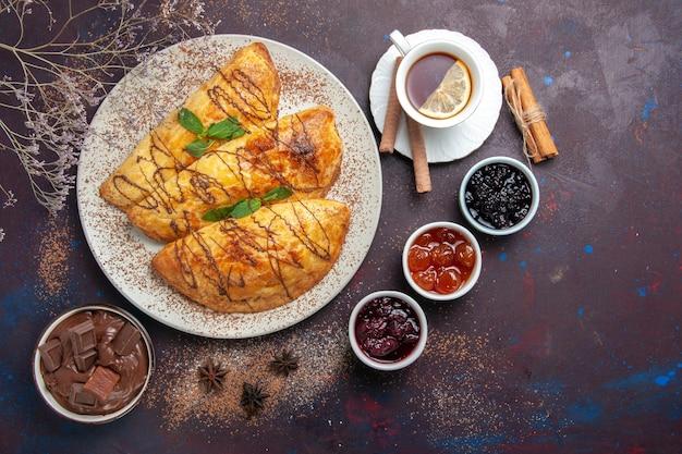 Vista dall'alto deliziosi pasticcini al forno con tazza di tè e marmellata su spazio viola scuro