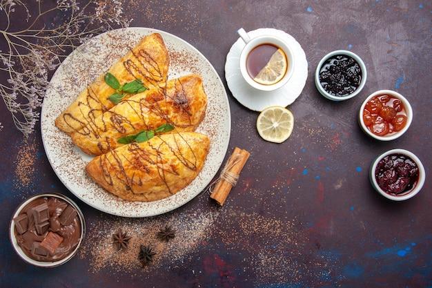 Vista dall'alto deliziosi pasticcini al forno con una tazza di marmellata di tè su uno spazio buio