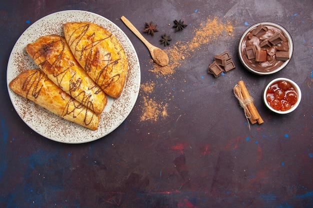 Vista dall'alto deliziosi pasticcini al forno con marmellata in uno spazio buio