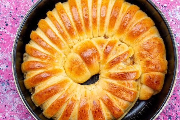 Vista dall'alto di deliziosi braccialetti di pasticceria al forno formati all'interno della padella su zucchero dolce e luminoso, biscotti di pasticceria