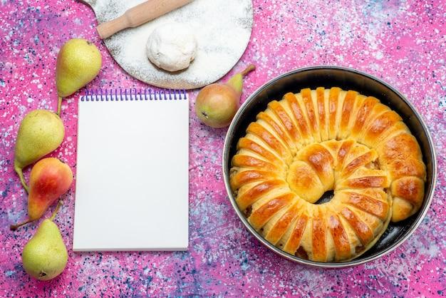 Vista dall'alto di deliziosi braccialetti di pasticceria al forno formati all'interno della padella con blocco note e pere sulla scrivania luminosa, zucchero dolce biscotto pasticceria