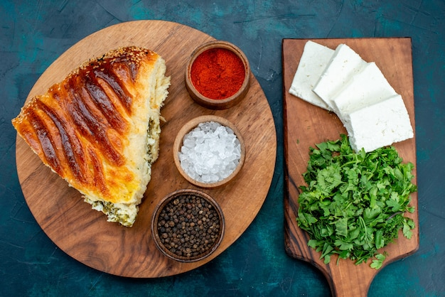 Top view delicious baked pastry sliced with greens filling with seasonings and white cheese on dark desk.