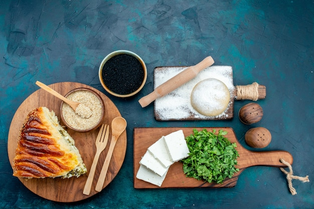 Top view delicious baked pastry sliced with greens inside along with fresh white cheese and greens on dark desk.