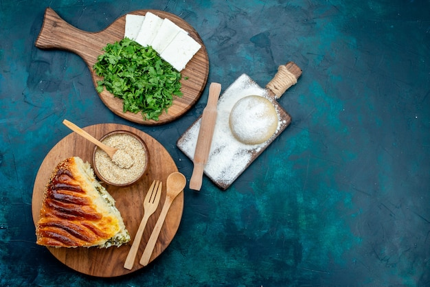 Top view delicious baked pastry sliced with greens inside along with white cheese and greens on dark background.