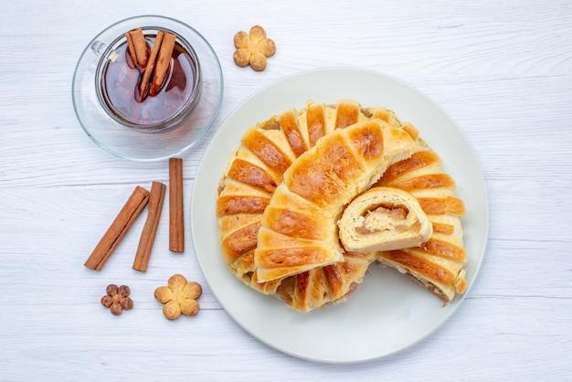 Vista dall'alto della deliziosa pasticceria al forno con ripieno dolce affettato e intero insieme a biscotti e tè sulla scrivania leggera, biscotto biscotto pasticceria dolce