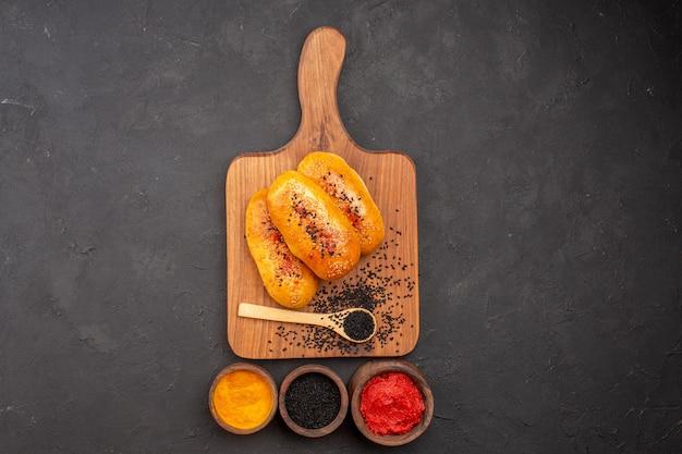 회색 배경 고기 파이 오븐 과자 케이크 빵에 다른 조미료와 오븐에서 신선한 상위 뷰 맛있는 구운 버거