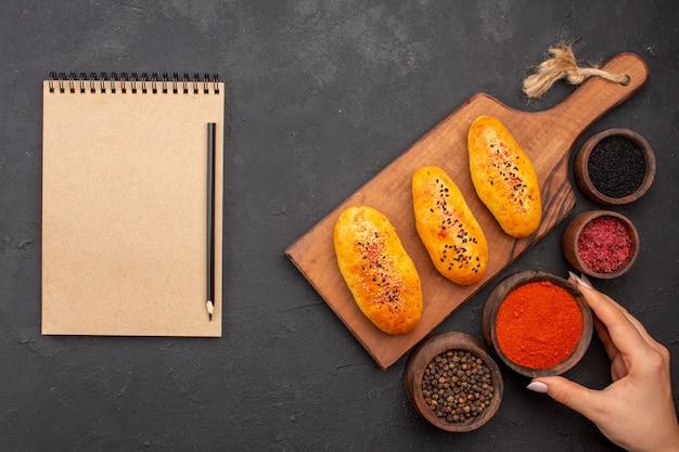 灰色の机の上の調味料とオーブンから新鮮なおいしい焼きたてのパテの上面図ミートパイオーブンペストリーケーキ焼き
