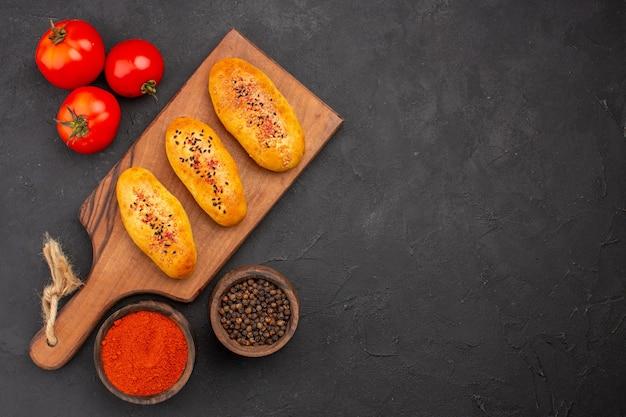 上面図灰色の背景にトマトとオーブンで焼きたてのおいしい焼きたてのパテパイオーブンペストリー生地ミートケーキ焼き