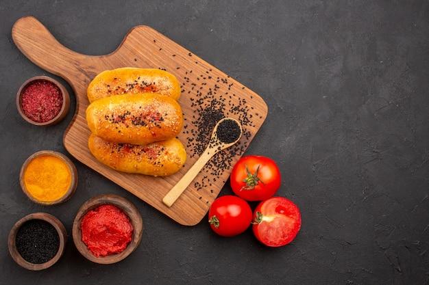 灰色の背景にさまざまな調味料とトマトを使ったおいしい焼きたてのパテの上面図ミートパイペストリーケーキ焼きオーブン