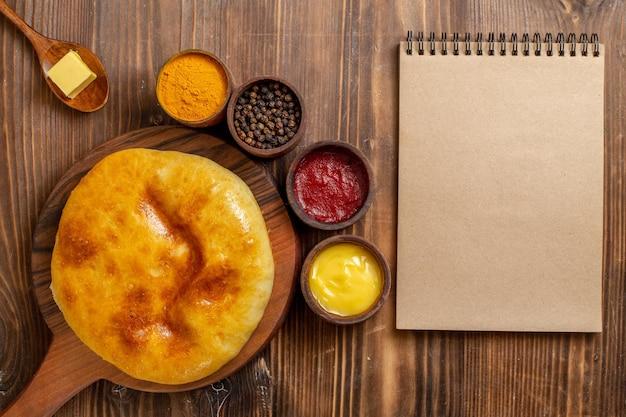 トップビュー茶色の木製デスクケーキにマッシュポテトと調味料を添えたおいしい焼きパイホットケーキパイ焼き生地ミール