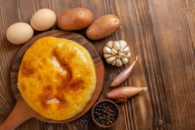 トップビュー茶色の木製の机の上にマッシュポテトが入ったおいしい焼きたてのパイホットケーキパイ焼き生地の食事