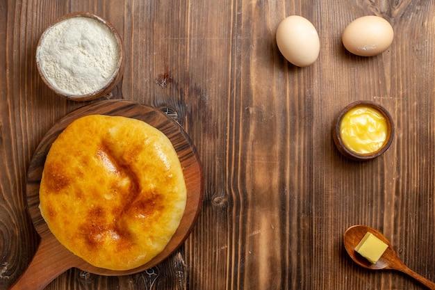 トップビュー茶色の木製デスクケーキにマッシュポテトを添えたおいしい焼きパイホットケーキパイ焼き生地ミール