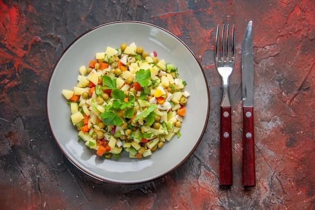 上面図フォークとナイフでプレート内のおいしい豆サラダ暗い表面の健康食事ディナー皿色スナックダイエットパン料理