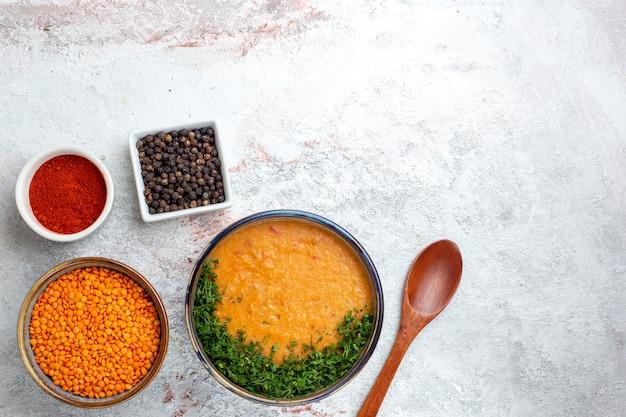 Vista dall'alto deliziosa zuppa di fagioli con verdure e condimenti sulla verdura della zuppa di cibo di superficie bianca