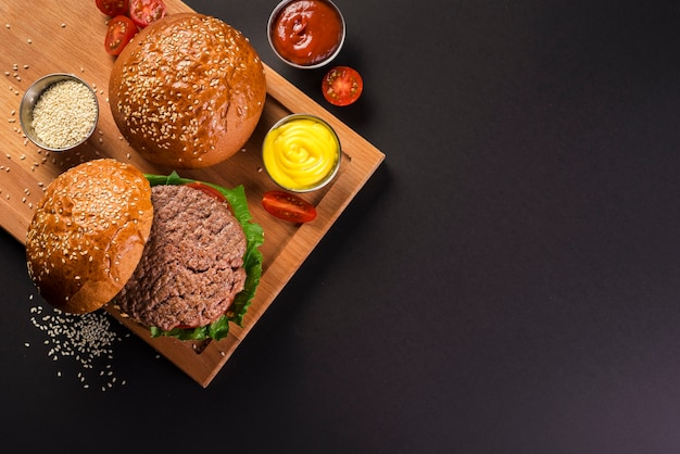 Top view delicious beef burgers with mustard
