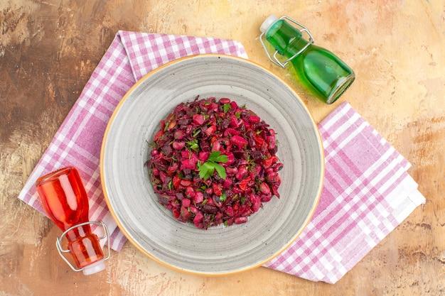 コピースペースのある木製のテーブルにオリーブオイルをまとったセラミックプレートの上面図おいしいビートサラダ