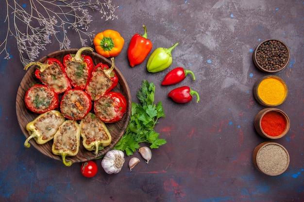 トップビューおいしいベルペッパー焼き皿ミンスミートと野菜をダークデスクでディナーフード焼き塩皿肉