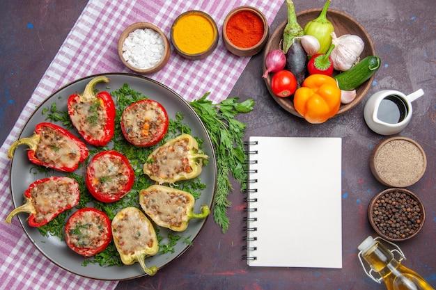 Vista dall'alto deliziosi peperoni gustosi piatti cucinati con carne e verdure su uno sfondo scuro piatto per la cena cibo piccante al pepe