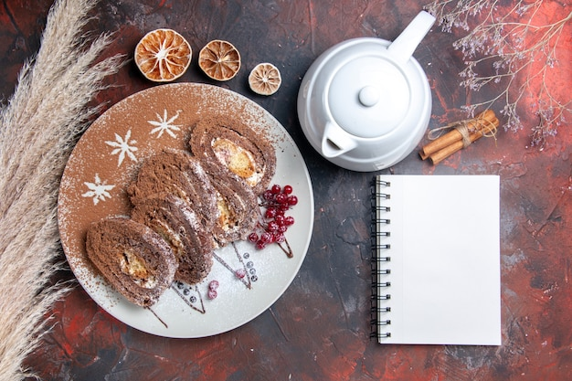 Vista dall'alto deliziosi rotoli di biscotti a fette di torte cremose su torta torta scura scrivania dolce